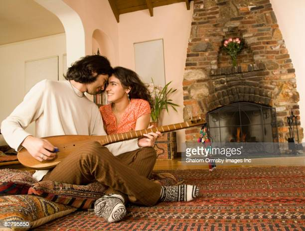 Multi-ethnic couple playing sitar on living floor