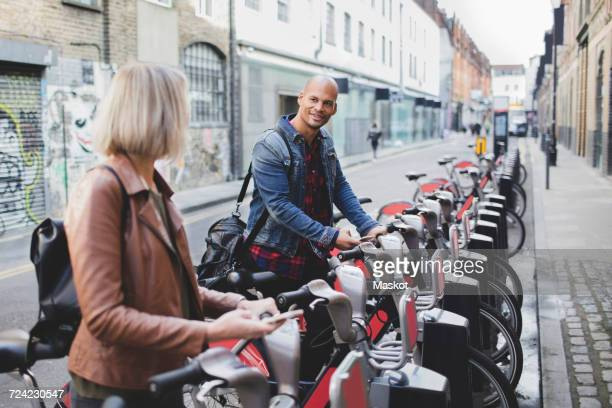 Multi-ethnic couple renting bicycles from bike share stand in city