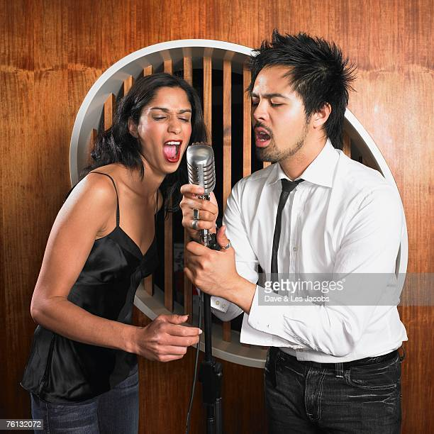 multi-ethnic couple singing into microphone - duet stock pictures, royalty-free photos & images