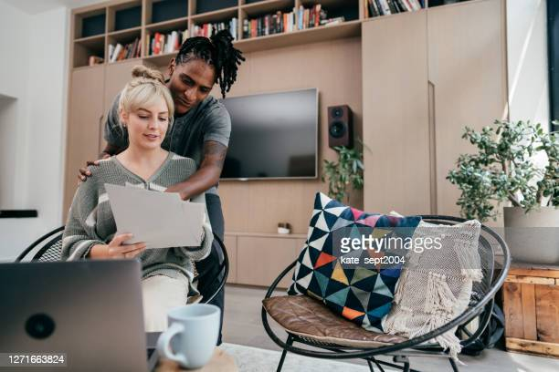 multi-ethnic couple sitting in the living room in front of computer with paper bills - borrowing stock pictures, royalty-free photos & images