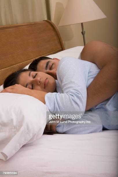 multi-ethnic couple sleeping in bed - abbracciarsi a letto foto e immagini stock