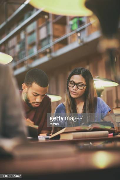 multi-ethnic couple studying in library - science photo library stock pictures, royalty-free photos & images