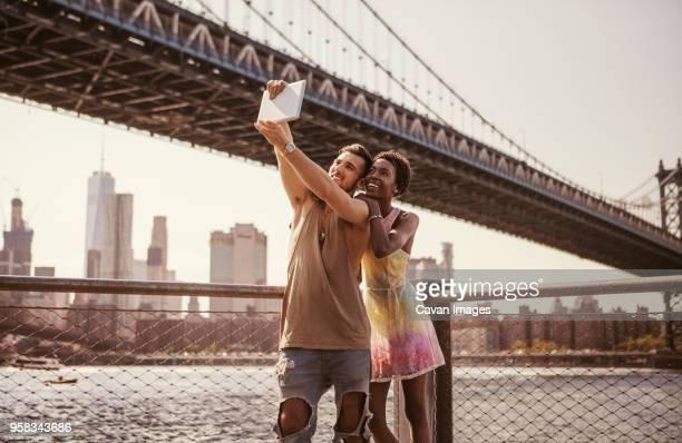 multi-ethnic couple taking selfie through tablet computer against manhattan bridge and city skyline - 人工建造物 ストックフォトと画像