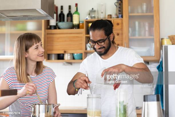 multi-ethnic couple talking and cooking in kitchen - sigrid gombert stock pictures, royalty-free photos & images