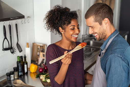 Multiethnic couple tasting food from wooden spoon 1158242307