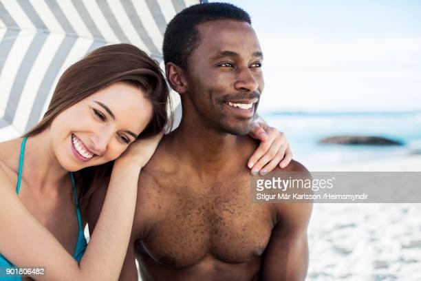 Multi-ethnic couple under parasol at beach