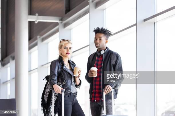 multi-ethnic couple waiting in airport lounge with coffee - izusek imagens e fotografias de stock