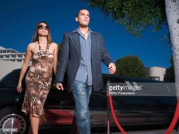 Multi-ethnic couple walking away from limousine