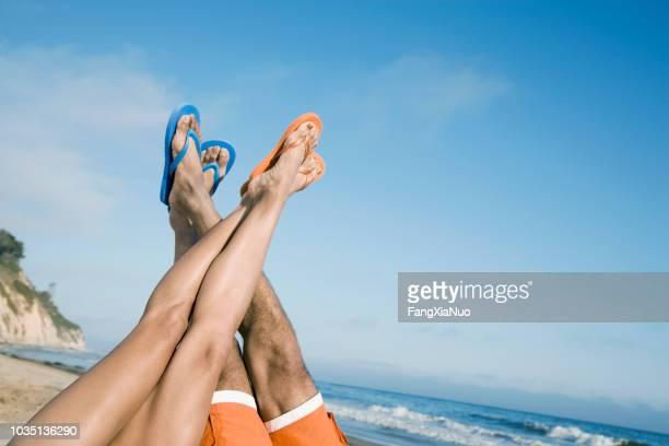 multi-ethnic couple with feet in air - ciabatta infradito foto e immagini stock