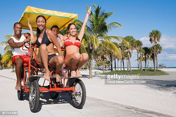 Multi-ethnic couples riding on pedal cart