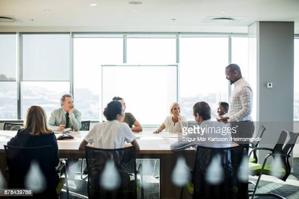 multi-ethnic coworkers discussing at office - business plan stock pictures, royalty-free photos & images