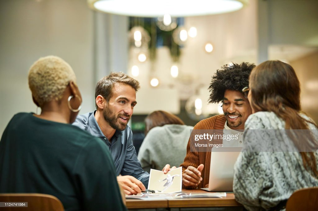Multi-ethnic coworkers discussing in office : Foto de stock