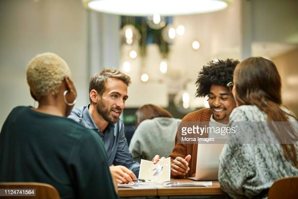 multi-ethnic coworkers discussing in office - werkplek stockfoto's en -beelden