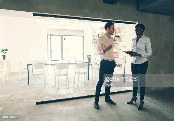 Multi-ethnic Coworkers talking in front of an office.