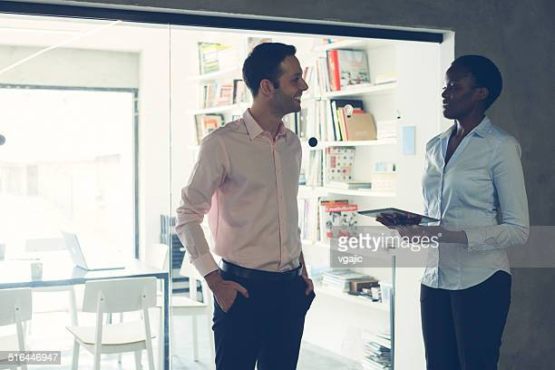 multi-ethnic coworkers talking in front of an office. - hands in pockets stock photos and pictures
