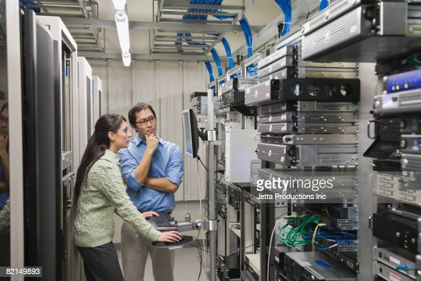 Multi-ethnic coworkers working in computer server room