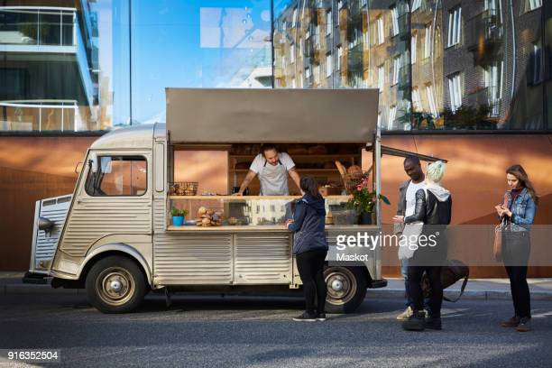 Multi-ethnic customers buying from owner in food truck against building