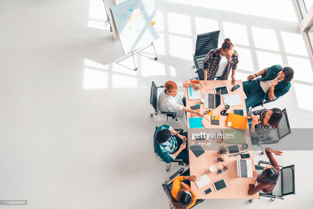 Multiethnic diverse group of business coworkers in team meeting discussion, top view modern office with copy space. Partnership professional teamwork, startup company, or project brainstorm concept : Stock Photo