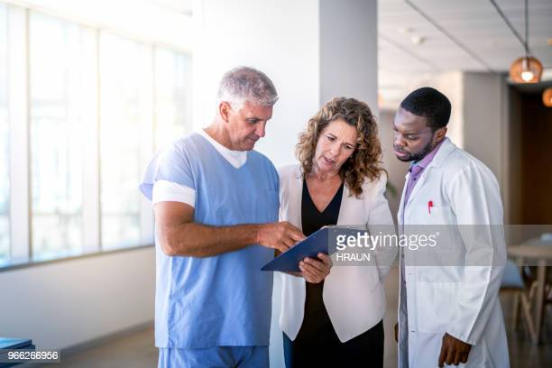 multi-ethnic doctors discussing over clipboard - medical chart stock pictures, royalty-free photos & images