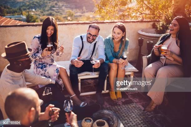 Multi-ethnischen elegante Freunde, trinken Wein und Bier im rustikalen cottage