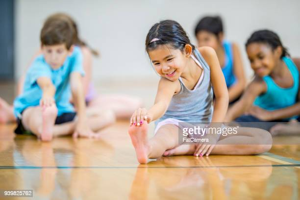 multi-ethnic elementary age group stretching - physical education stock pictures, royalty-free photos & images