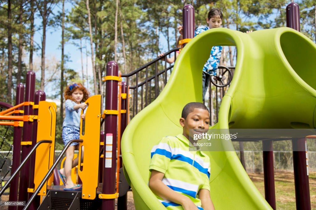 Multi-ethnic elementary school children playing on playground at park. : ストックフォト