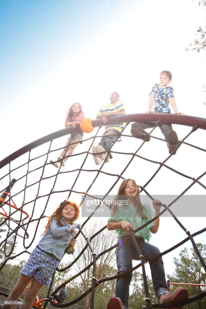 Multi-ethnic elementary school children playing on playground at park. : Stock-Foto