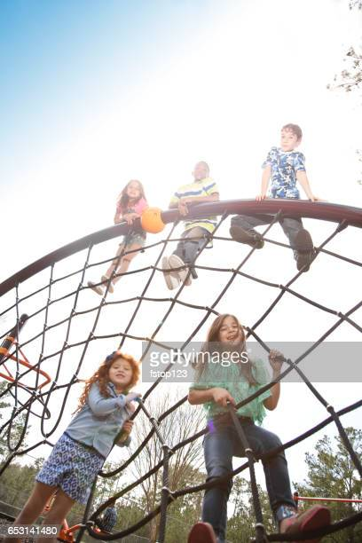 Multi-ethnic elementary school children playing on playground at park.