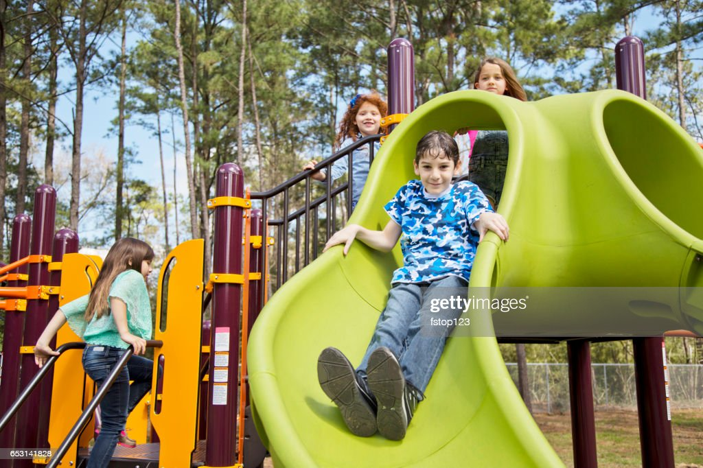 Multi-ethnic elementary school children playing on playground at park. : Stockfoto