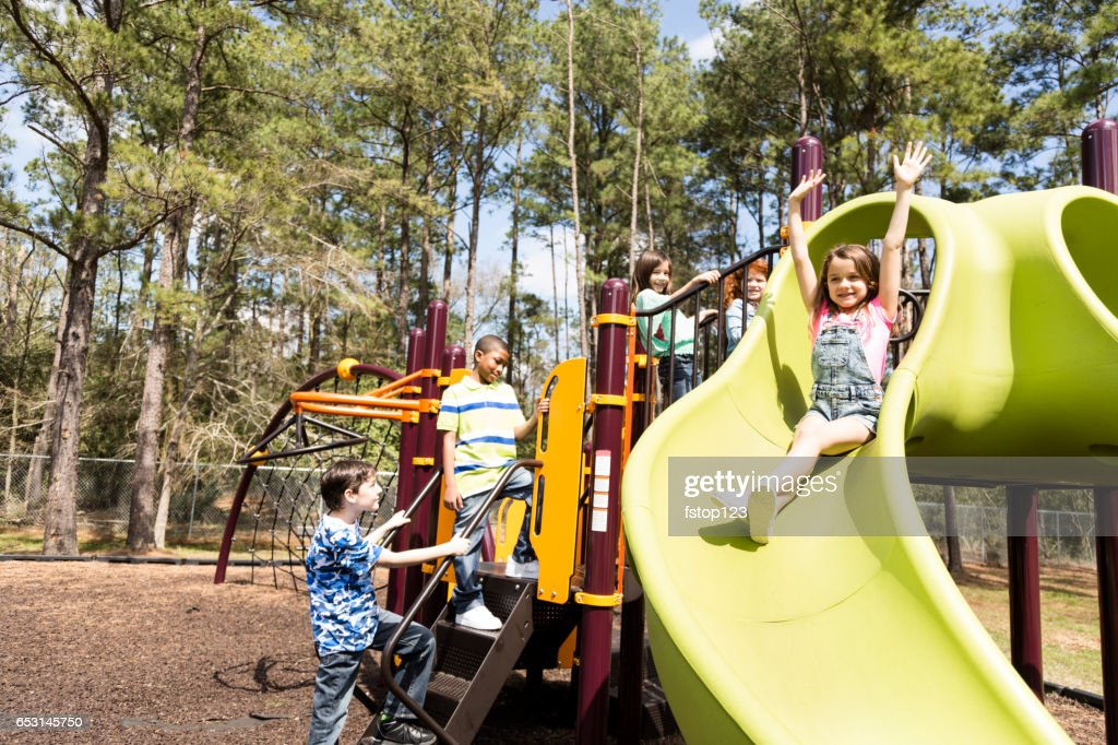 Multi-ethnic elementary school children playing on playground at park. : Stock Photo