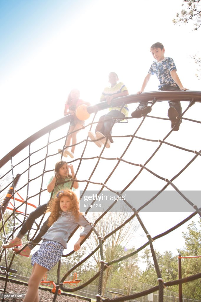 Multi-ethnic elementary school children playing on playground at park. : Photo