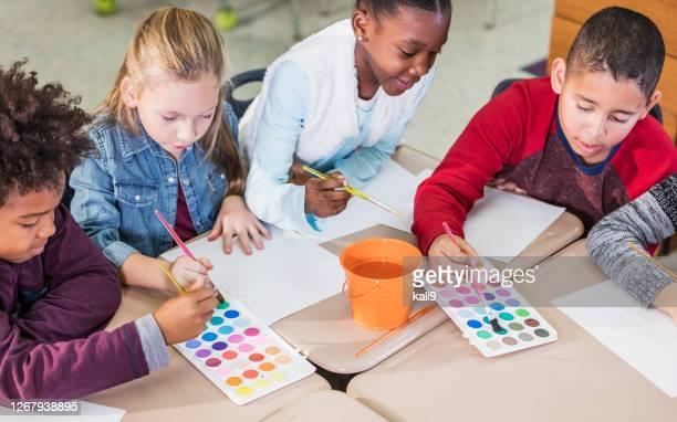 multi-etnische basisschoolleerlingen in kunstklasse, het schilderen - 6 7 jaar stockfoto's en -beelden
