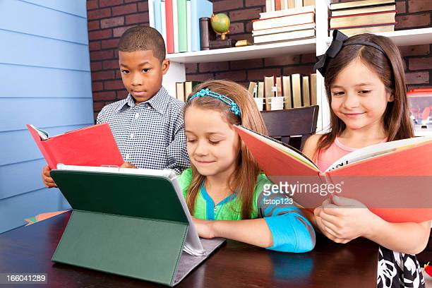 Multi-ethnic elementary students. School classroom. Digital tablet and books.