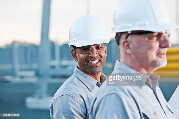 multi-ethnic engineers at industrial site - work helmet stock pictures, royalty-free photos & images