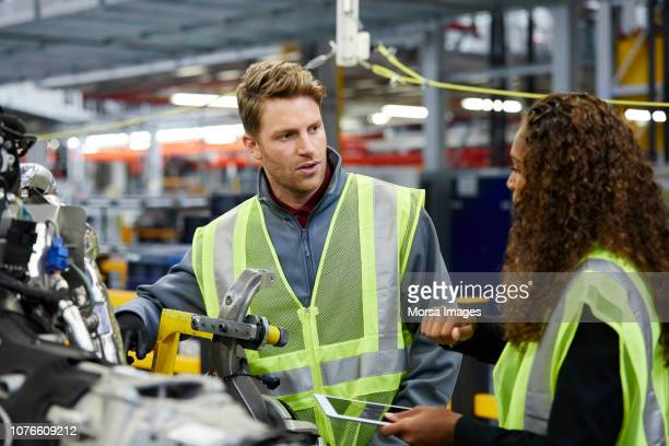 multi-ethnic engineers discussing over car chassis - mechanical engineering stock pictures, royalty-free photos & images
