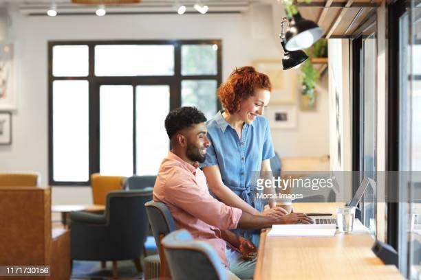 multi-ethnic entrepreneurs discussing over laptop - etnia imagens e fotografias de stock