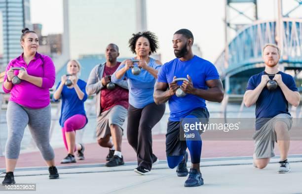 Multi-ethnic exercise class,  lifting kettlebell