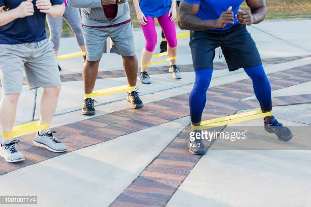 Multi-ethnic exercise class, resistance bands on ankles