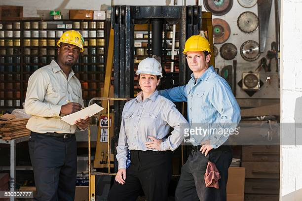 Multi-ethnic factory workers with female boss