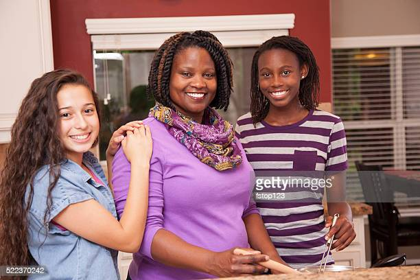 Multi-ethnic family at home cooking together in kitchen.