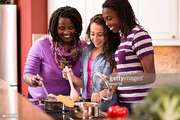 multi-ethnic family at home cooking together in kitchen. - african american family dinner stock photos and pictures