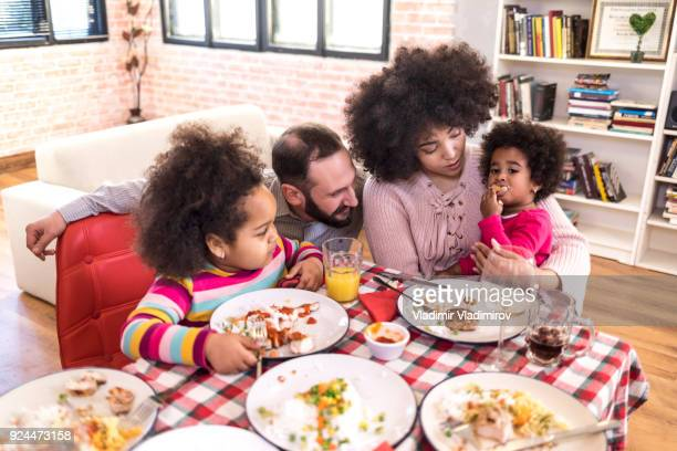 multi-ethnic family at home dinning - family at home stock photos and pictures