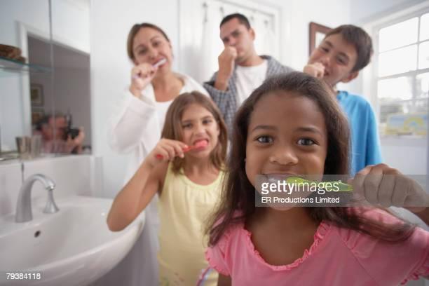 Multi-ethnic family brushing teeth