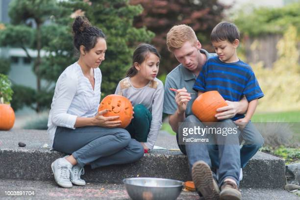 multiethnic family carving pumpkins together - carving craft product stock pictures, royalty-free photos & images