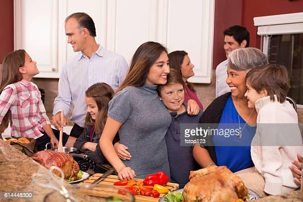 Multi-ethnic family cooks Thanksgiving, Christmas dinner in grandmother's home kitchen.