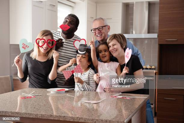 multi-ethnic family doing photobooth during valentine's day - valentines african american stock pictures, royalty-free photos & images