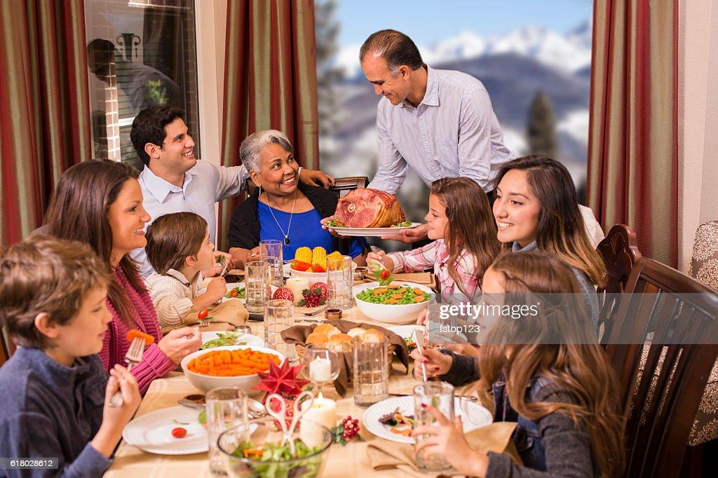 Multi-ethnic family enjoying Christmas dinner at grandmother's home. : Stock Photo