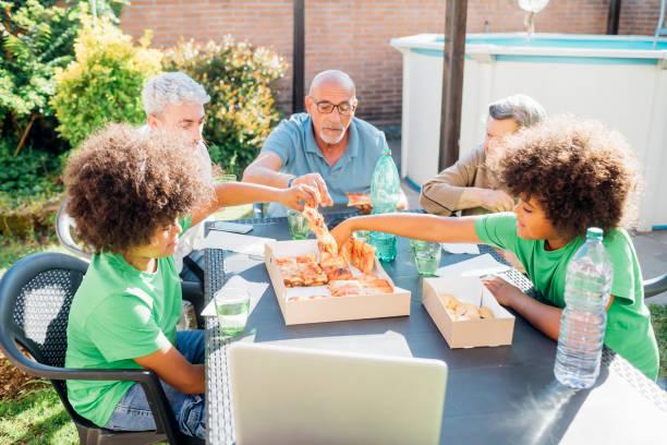 Multi-ethnic family enjoying snacks on table in back yard