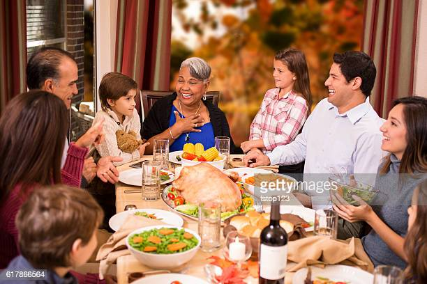 multi-ethnic family enjoying thanksgiving dinner at grandmother's home. - black family dinner stock photos and pictures