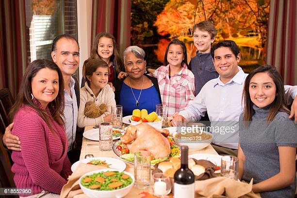 Multi-ethnic family enjoying Thanksgiving dinner at grandmother's home.